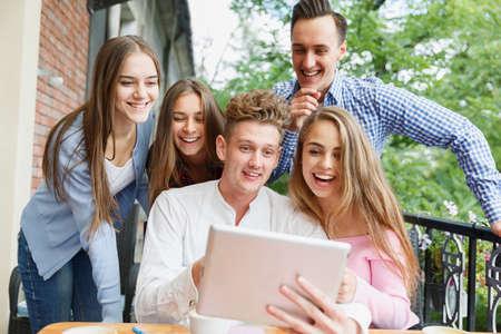 Vrolijke vrienden enthousiast over nieuwe tablet op de achtergrond van de koffie. Verbinding en technologie concept. Stockfoto