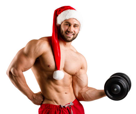 Strong ans sexy Santa Claus with muscular body in red and white christmas santa hat, isolated, white background