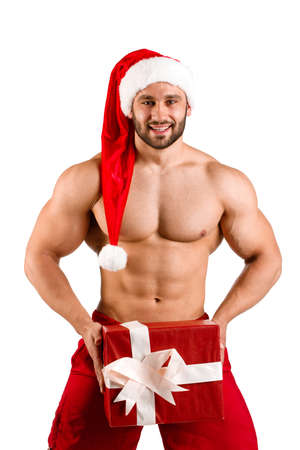 Smiling fitness white guy wearing Santa Claus hat with muscular body and big gift box, isolated