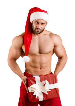 Christmas fitness white guy wearing Santa Claus hat with muschular body and big gift box, isolated Stock Photo