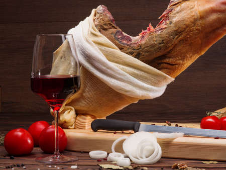 salamanca: Iberian ham pata negra from Spain, tomatoes, onion rings and red wine glass. Horizontal Closeup image. Whole Mediterranean traditional jamon on a wooden stand