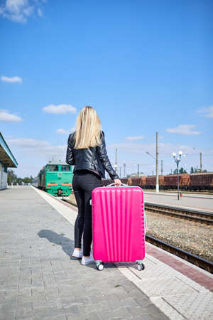 A girl with a pink suitcase is standing at the railway station Stock Photo
