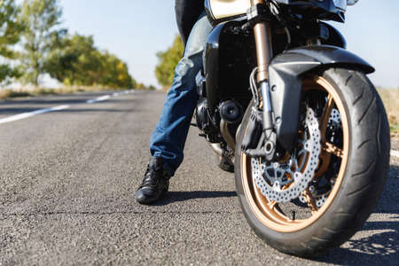 A close-up of a motorcycle stands on the road with its owner alone