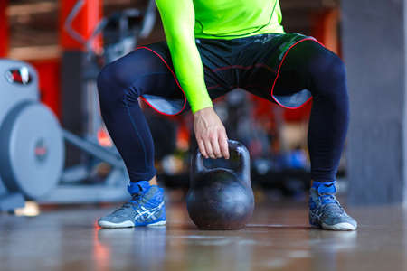 A man in a green sweater in the gym with weights. Stock Photo