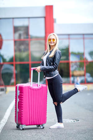 A girl with a pink suitcase stands on the street close up Stock Photo