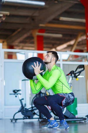 A man in the gym crouches with a ball.
