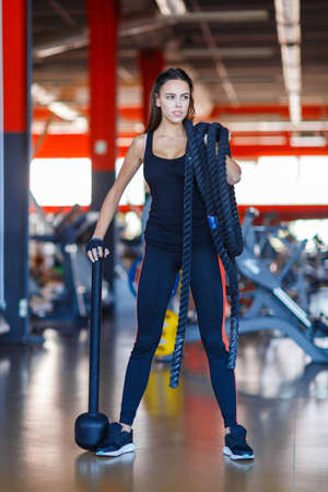 A young girl poses in the gym with a rope on her shoulder and a hammer. Stock Photo