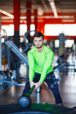 A young man is training in the gym using a hammer and a tire. Stock Photo