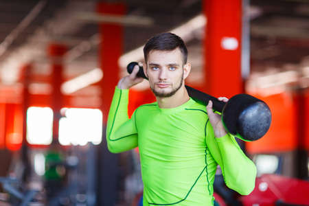 A young man in green posing in the gym with a hammer Stock Photo