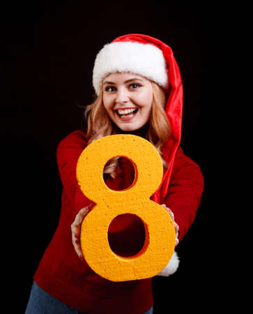 Attracive girl in a Santa costume holding a number eight on a black background. 2018 celebrating concept.