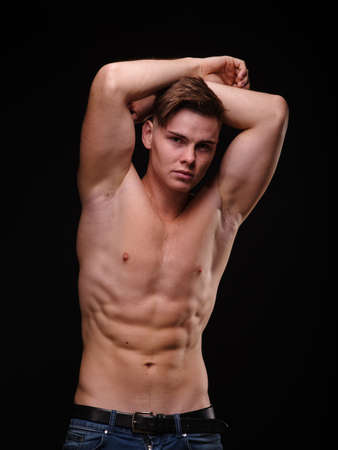 Sexy, shirtless, expressive young man on a black background. Workout, training, sports concept.