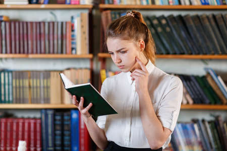 Portrait of a young girl who is reading a book in the library.