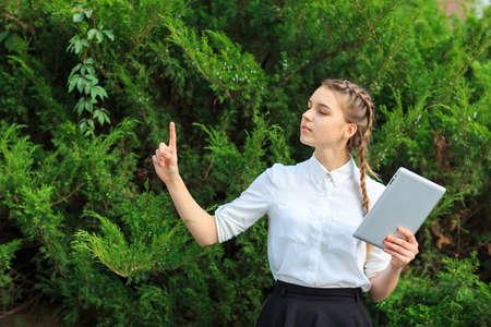 une jeune fille brune est assise dans un parc avec une tablette