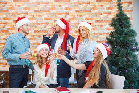 Equipo de oficina feliz en una fiesta de Navidad bebiendo en un fondo festivo. Navidad animando concepto.