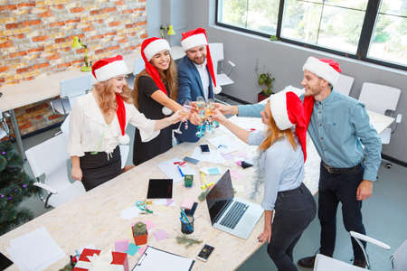 Office team drinking on Christmas on the office background. Xmas party. Christmas champagne concept.