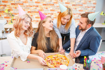 A group of men and women working in the office, eating pizza in a festive mood. Stock Photo