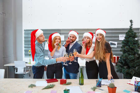 Young happy friends celebrating New Year on a blurred background. Christmas party with Santa hats concept.