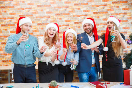 Cheerful Christmas friends holding sparklers on the office background. New Year wishes concept.