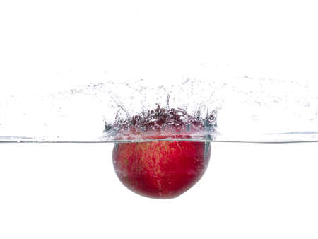 Pomegranate fall in water. Drops of water. Isolated white background