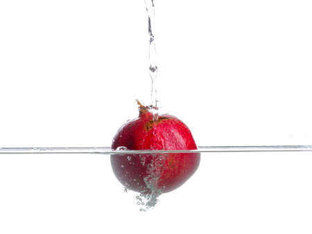 Pomegranate fall in water. Photo in action. Drops of water. Isolated white background