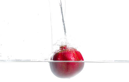 Pomegranate fall in to water. Drops of water. Isolated white background Stok Fotoğraf