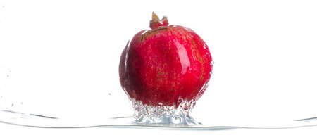 Pomegranate came from water. Drops of water. Isolated white background. Horizontal