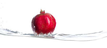 Pomegranate on water surface. Drops of water. Isolated white background