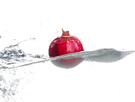 Pomegranate fall in water. Drops of water. Isolated garnet image on white background
