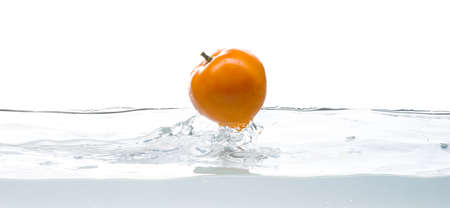 Yellow tomato fall in water. Photo in action. Drops of water. Isolated white background Stock Photo