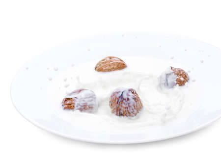 Walnuts falling in a white bowl with milk. Isolated photo on a white background. A drop of milk. frozen time Stok Fotoğraf