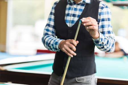 The player rubs the cue with special chalk