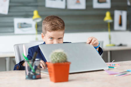 A small businessman opens a laptop in his place Stock Photo
