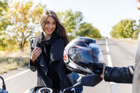 A motorcyclist passes a girls helmet for a safe ride Stock Photo