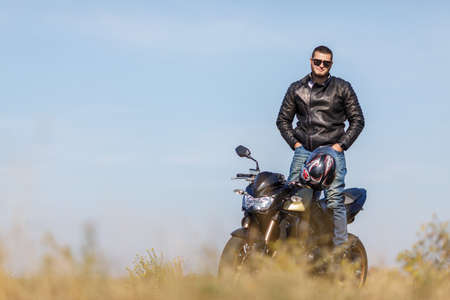 A handsome motorcycle stands on the road with its owner alone Stock Photo