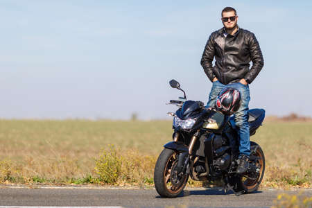 rejas de hierro: A handsome motorcycle stands on the road with its owner alone Foto de archivo