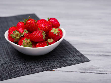 Fresh ripe fruits on a gray wooden table. Sweety red strawberries summer fruits on a gray background. Close-up of strawberry. Food concept. Stock Photo