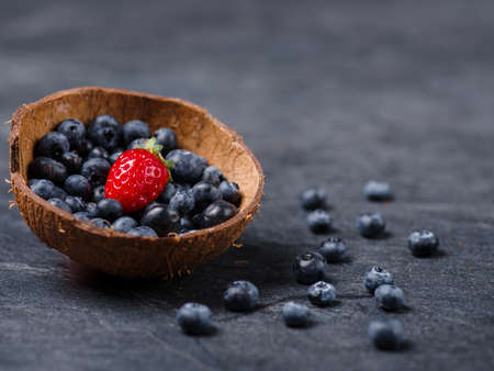 vitamin rich: Fresh ripe fruits on a gray background. Sweety red strawberries and blueberries on a dark background. Copy space. Close-up of fruits. Food concept.