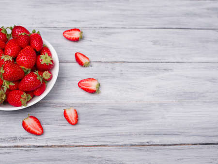 Fresh ripe fruits on a gray wooden table. Sweety red strawberries summer fruits on a gray background. Copy space. Close-up of strawberry. Food concept. Stock Photo
