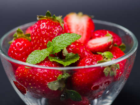 Fresh ripe fruits. Sweety red strawberries summer fruits in a glass bowl on a gray background. Copy space. Close-up of strawberry. Food concept. Stock Photo