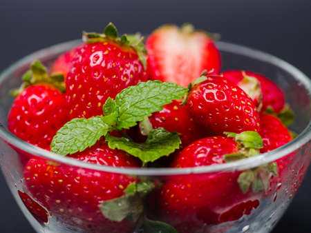 desk: Sweet fresh strawberries in bowl on a gray background. Food concept.