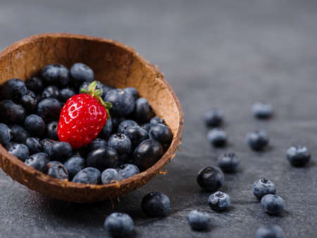 Sweet fresh strawberries and blueberries in bowl on a dark background. Food concept.