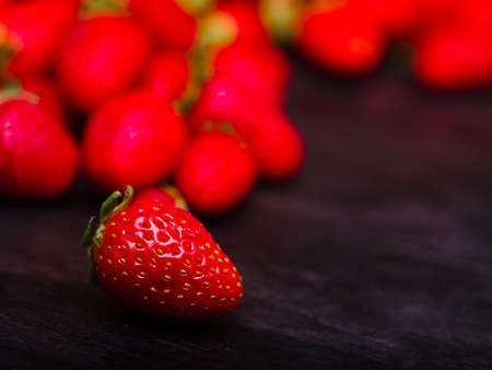 Sweet fresh strawberries on a dark wooden table. Food concept.