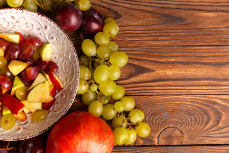 Delicious salad in a plate of fruit on a wooden table.