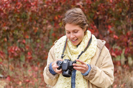 A young girl in an autumn forest with a camera. Stock Photo