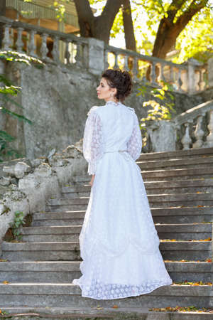Beautiful young bride in wedding dress on the steps.