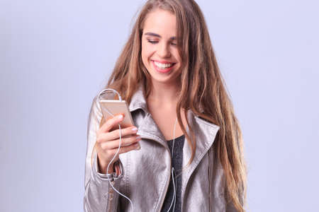 A beautiful girl on a gray background listens to music from her phone.