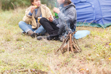 Couple relaxing in the forest. A loving couple is sitting in front of the tent.