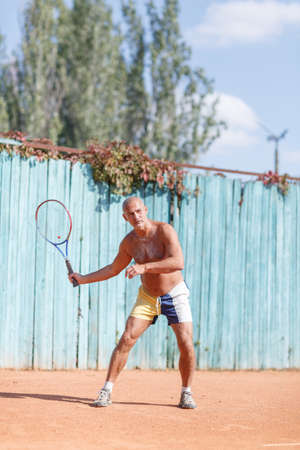 Older men hit the ball on the tennis court.