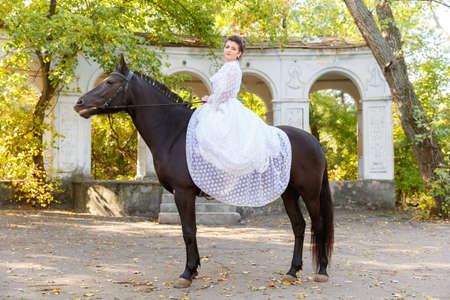 Beautiful bride in a dress riding a horse.