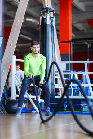 Young athletes man does exercises at the gym. Sport concept. Stock Photo